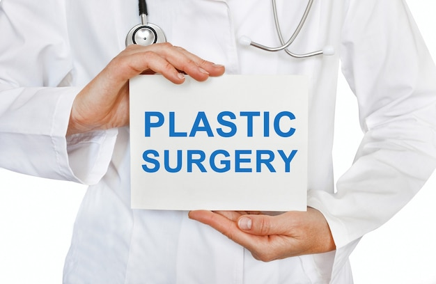 Plastic surgery card in hands of medical doctor