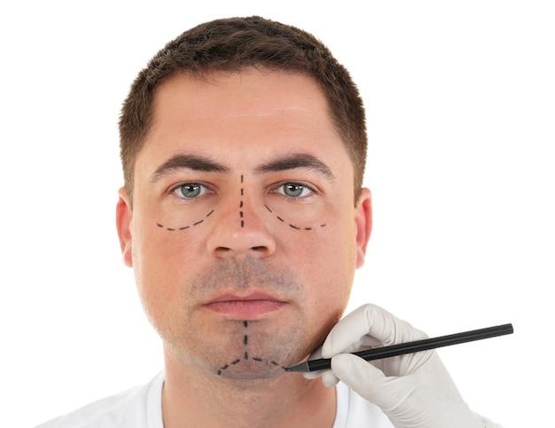 Концепция пластической хирургии. рука в перчатке, маркировка мужского лица