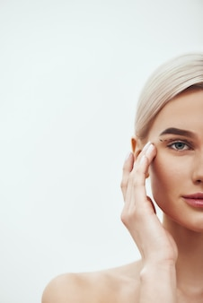Plastic surgery operation cropped photo of pretty and young blonde woman touching her face with