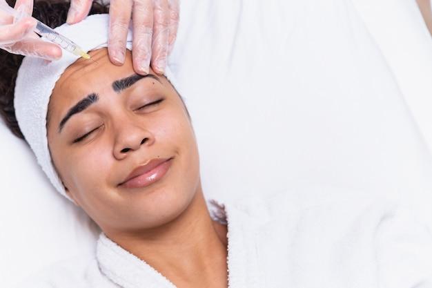 形成外科。美容クリニック、クローズアップ、コピースペースの眉間ゾーンでボトックス注射を受けている若いアフリカの女性。額にボトックス注射を受けている若いアフリカ人女性。