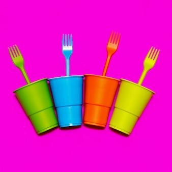 プラスチック製の食器。最小限。色とりどりのメガネとフォーク