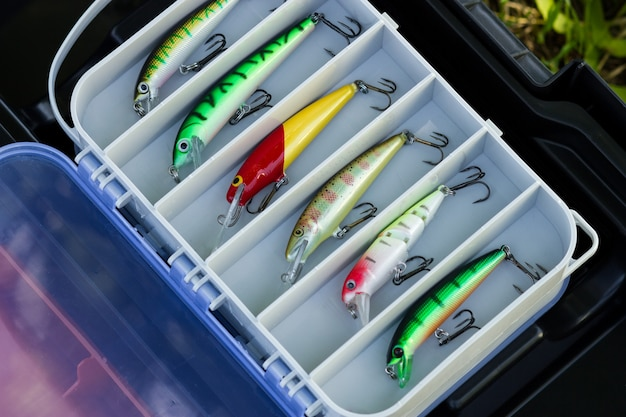 Plastic tackle box with various fishing plastic baits and lures top view hobby and leisure concept
