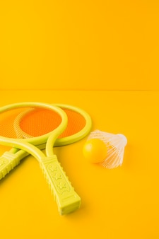 Plastic tennis racket with ball and shuttlecock against yellow backdrop