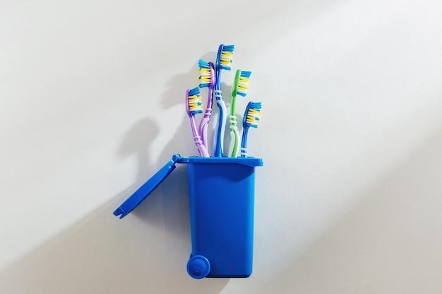 Пластиковые зубные щетки в мусорном ведре на белом фоне. концепция переработки пластика.