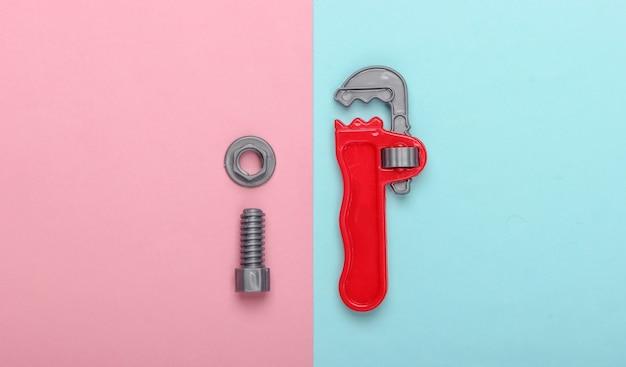 青ピンクのパステル背景にボルトでプラスチック製のおもちゃのモンキーレンチとナット。上面図