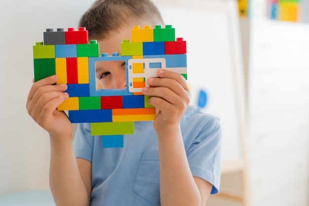Plastic toy blocks, designer children's toys. bright building blocks shape heart in children's hands.