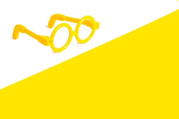 白と黄色の背景に黄色のプラスチック製のおもちゃのメガネ。テキスト用の空き容量