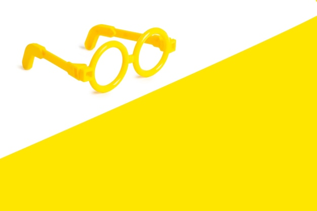 Plastic toy glasses of yellow color on a white and yellow background. free space for text