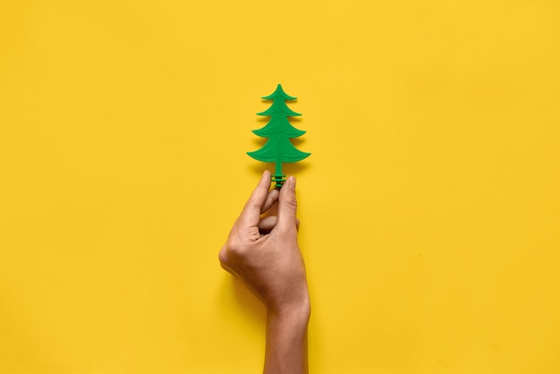 Plastic toy pine wood tree on yellow . minimal flat laychristmas season. copyspace