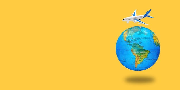 Plastic toy plane on the globe. flight travel concept. travel by airplane. takeoff and landing of the aircraft. return home from flight. long wide banner with copy space