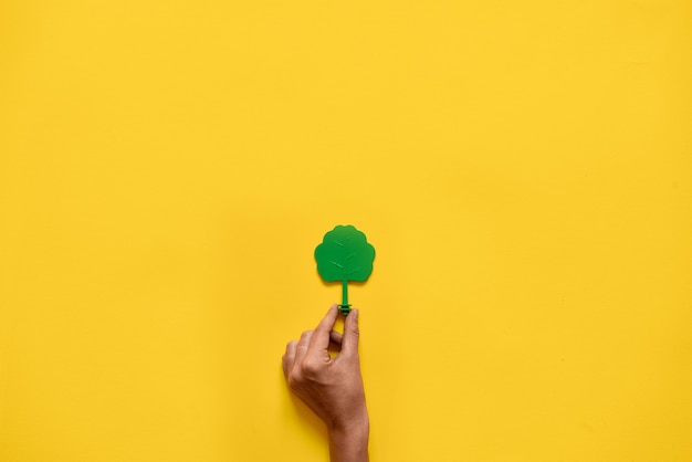 Plastic toy wood tree on yellow . minimal flat lay ecology environment