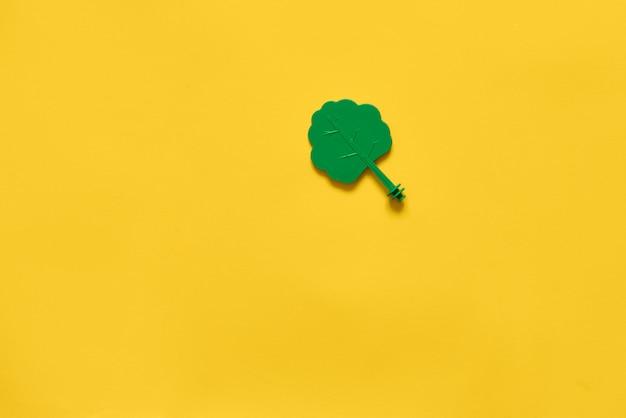Plastic toy wood tree on yellow . minimal flat layecology environment