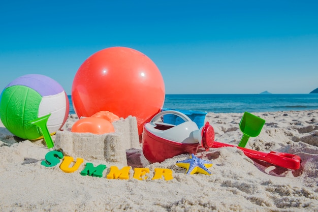 Plastic toys and ball on sand