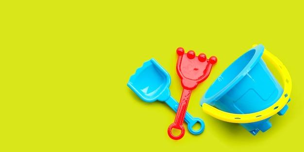 Пластиковые игрушки, лопата и ведро для песка на зеленом фоне. летний фон концепция