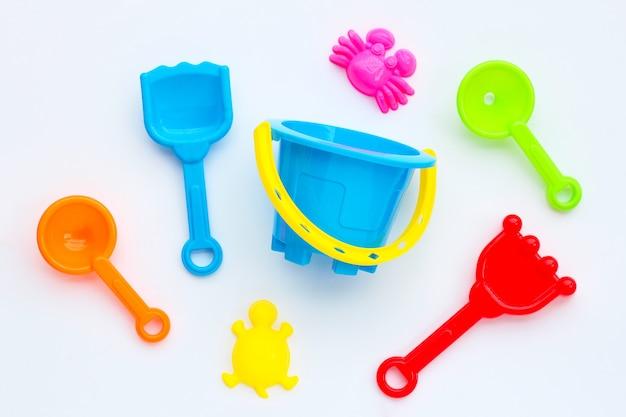 白い表面の砂のためのプラスチックのおもちゃ、シャベル、バケツ