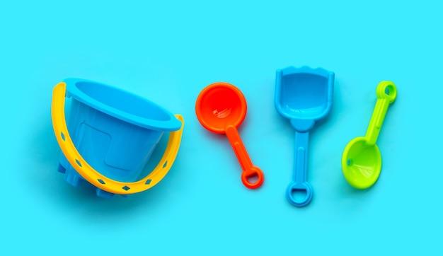 青い背景にプラスチックのおもちゃ、シャベル、バケツ。