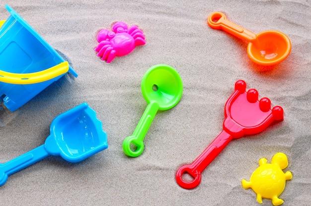 砂の上のプラスチック製のおもちゃ、シャベル、バケツ。