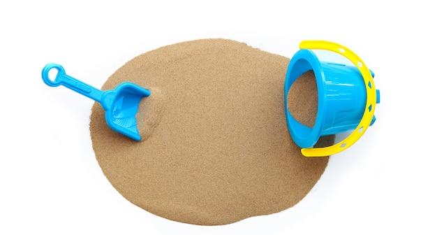 プラスチック製のおもちゃ、シャベル、バケツ、白い表面に砂。
