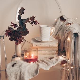 On a plastic transparent chair - warm bedspread, a cup of tea on books and a candle with autumn leaves. autumn winter concept.