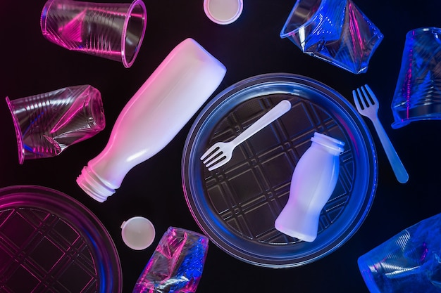 Plastic transparent tableware in neon lighting on black background. environmental pollution concept