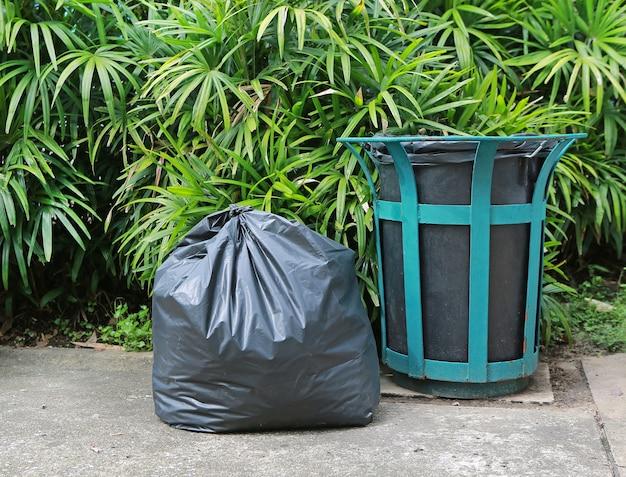 Plastic trash bags and rubbish bin in a park.