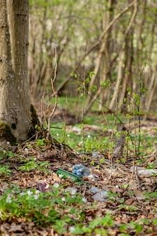 森の中のプラスチックのゴミ。隠れた自然。草の中に横たわるプラスチック容器