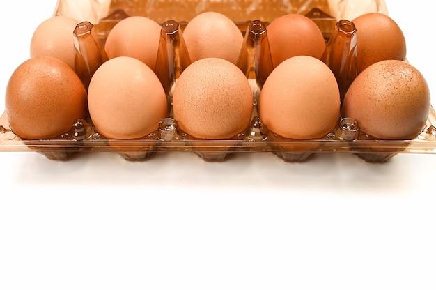 孤立した白い背景の上の鶏の卵とプラスチックトレイ。高品質の写真