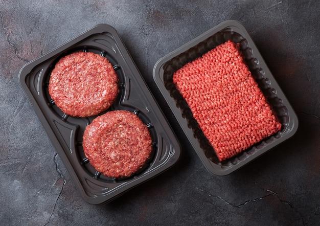 Пластиковый поднос с сыром фаршем домашнего мясного котлета из говядины со специями и зеленью. вид сверху и.