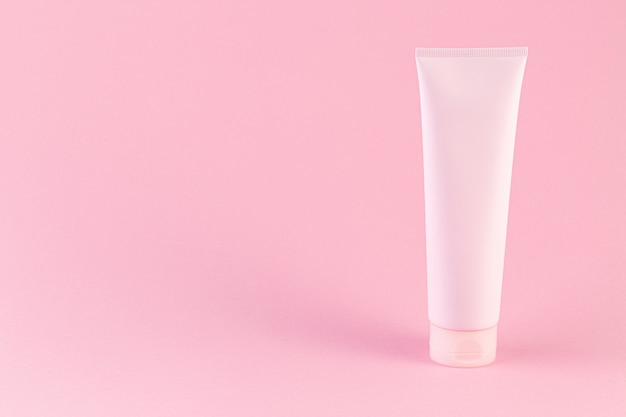 Plastic tube with face or body cream on pastel pink background with copy space.
