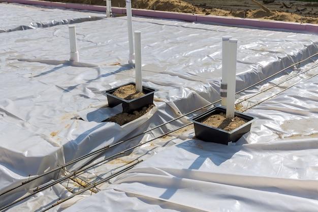 바닥에 기초의 배관 pvc 파이프가 있는 슬래브의 플라스틱 증기 장벽
