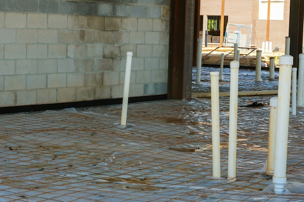 Plastic vapor barrier on slab with plumbing pvc pipes of foundation in the ground