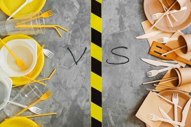 플라스틱 대 지속 가능한 식기 선택 개념. 흰색과 노란색 플라스틱 및 나무기구의보기 사진 위의 회색 배경에 비교.