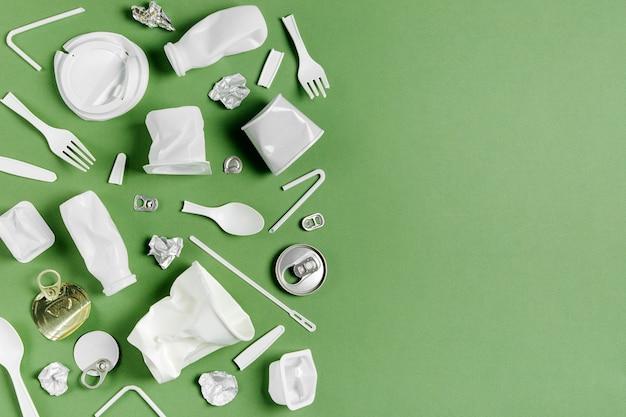 Сбор пластиковых отходов на зеленом фоне. концепция переработки пластика и экологии. плоская планировка, вид сверху