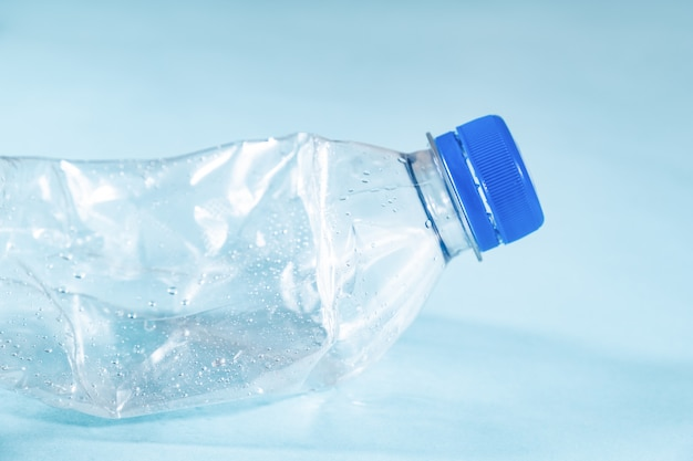 Plastic waste concept: discarded crumpled water bottle in blue surface, detailed view.