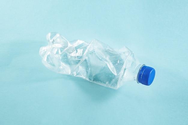 Концепция пластиковых отходов: выброшенная мятая бутылка с водой на синей поверхности