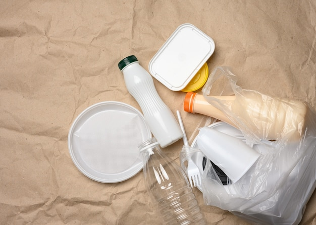 Plastic waste from life on the background of brown kraft paper, environmental pollution, top view