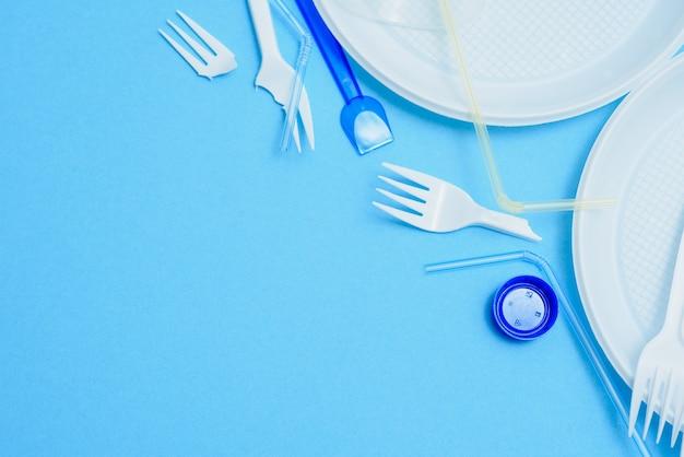プラスチック廃棄物、青色の背景にプラスチック調理器具、フラットレイアウト。使い捨てのプラスチックにノーと言う
