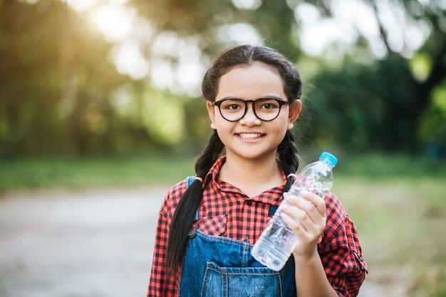 Plastic water bottle in girl hand
