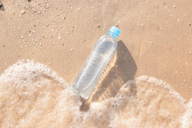 ビーチのプラスチック製の水筒は波で洗われます。上面図、フラットレイ。