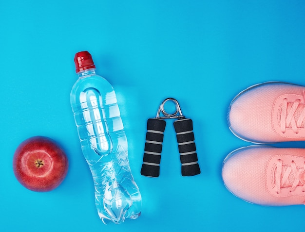 Plastic water bottle, red ripe apple and sports expander