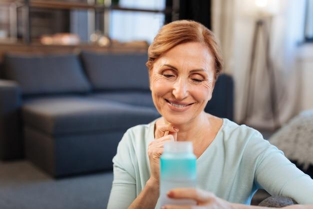 プラスチック製の水筒。水のボトルで床に座っている間彼女の毎日のトレーニングに満足している疲れた大人の女性