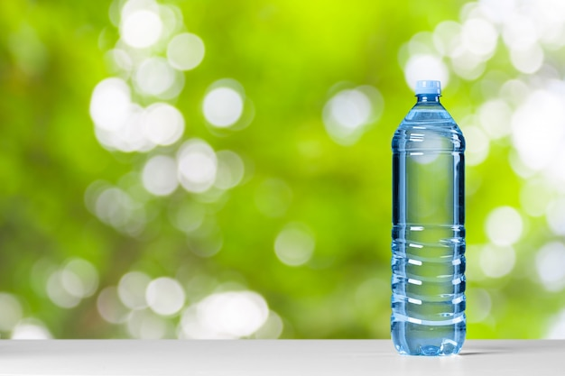 Plastic water bottle with blue cap on the wooden table