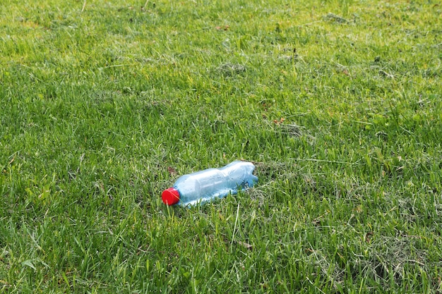 A plastic water bottle with a red cap lies on a newly trimmed lawn. concept of littering of the environment.