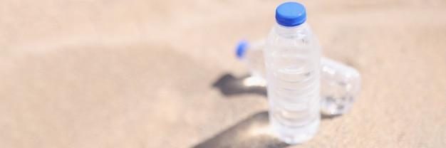 Plastic water bottles standing on hot sand closeup