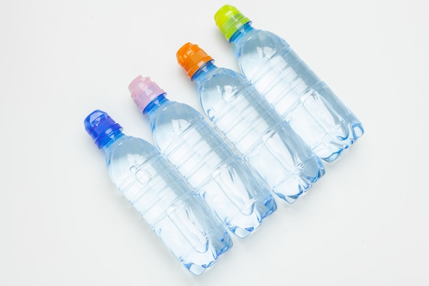 Plastic water bottles with caps of different colour on the  table