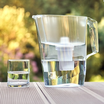 Пластиковый кувшин для фильтрации воды и чистый стакан с чистой водой на фоне летнего сада в солнечный теплый летний вечер в сельской местности