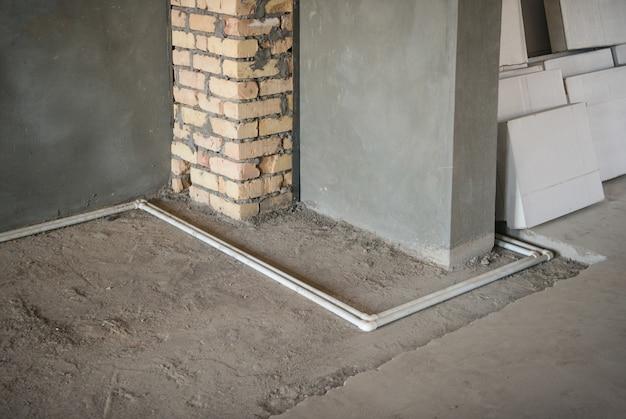 Пластиковые водопроводные трубы на полу и оштукатуренные стены в новом доме. первичный ремонт в комнате