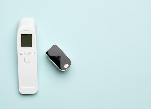 Пластиковый белый электронный бесконтактный термометр и измеритель кислорода в крови, синий фон