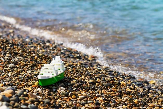 Пластиковая бело-зеленая игрушка лодка на берегу моря. галечный пляж.
