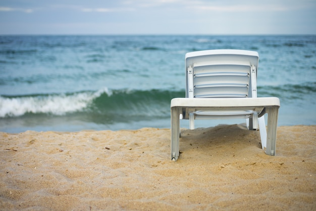 Plastic white lounge chair on empty beach